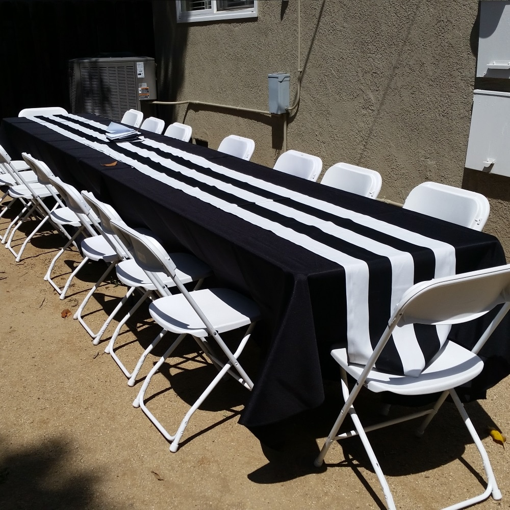 Rectangular Banquet tables with black tablecloths and white folding chairs for rent from Big Blue Sky Party Rentals