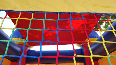 Inflatable Mini Bounce House Rental - close up view of the colorful net on window.