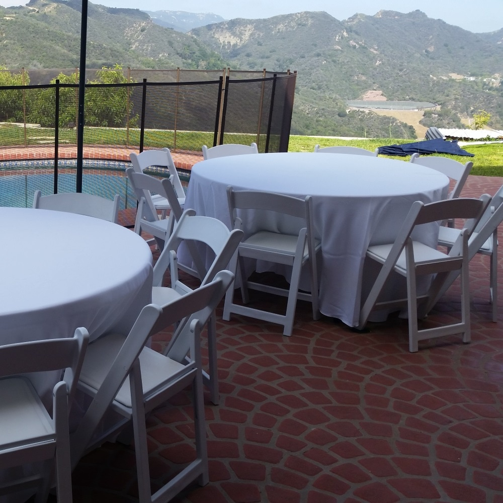 Round tables with white tablecloths for rent with outdoor White Garden Chairs from Big Blue Sky Party Rentals